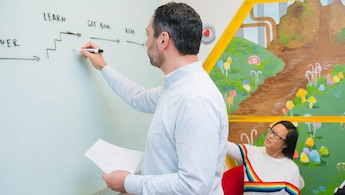 Man writing on a whiteboard while meeting with a woman in a fun room