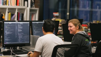 A female and male engineer programming together at a coworking desk